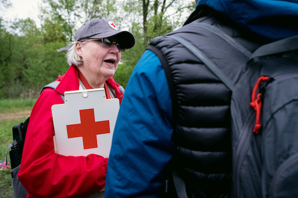 A woman holds a clipboard with a large red cross