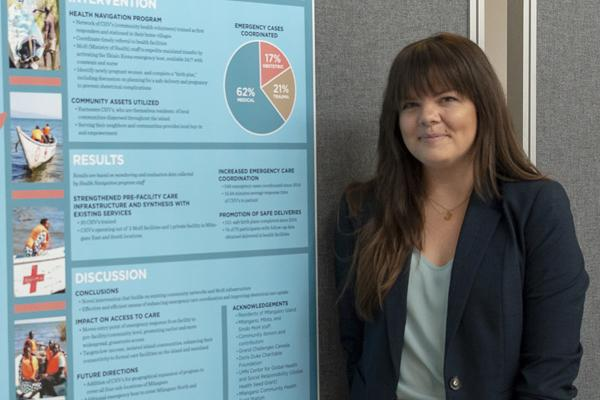 A woman stands next to her research poster
