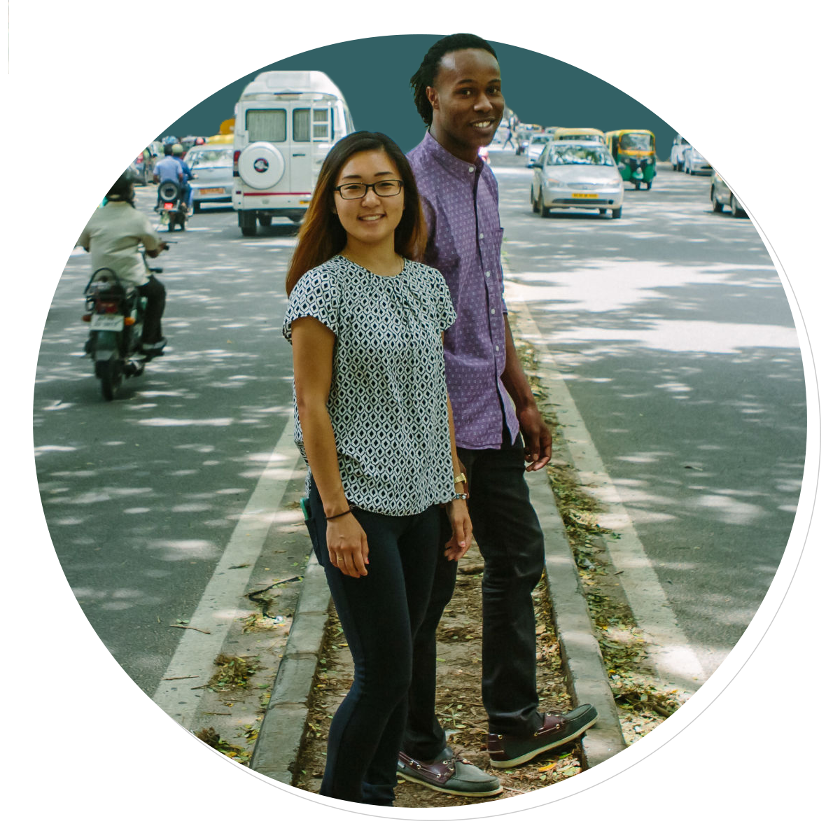 Two people stand in the median of a road