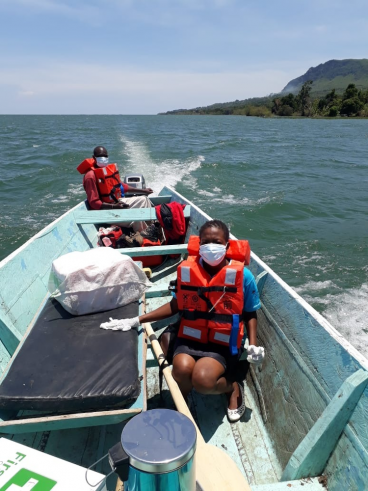 People with life jackets in a boat on a lake