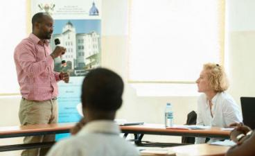 A man speaking into a microphone to a classroom showing 2 other people